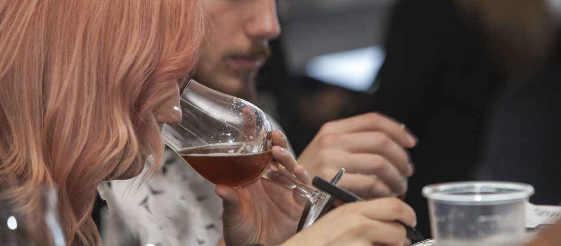 Valparaiso, Chile - march 31, 2018: one of many people (woman) tasting and smelling amber ale beer at a tasting to learn, at a beer fair in valparaiso, chile